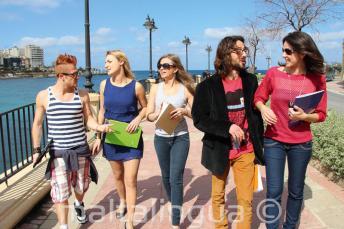 Sprachschüler üben Englisch nach dem Unterricht neben der St Julians Bay, Malta