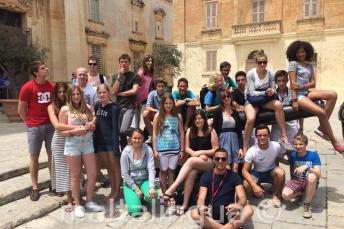 Junge Sprachschüler sitzen auf einer Kanone in Mdina
