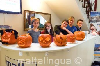 Junge Sprachschüler mit ausgehöhlten Halloween Kürbissen