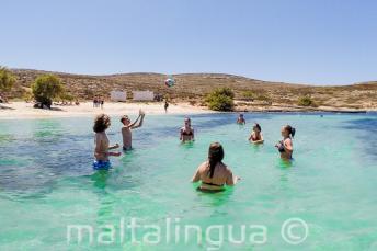 Junge Sprachschüler spielen Volleyball am Strand