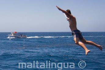 Ein Sprachschüler macht einen Sternsprung vom Boot