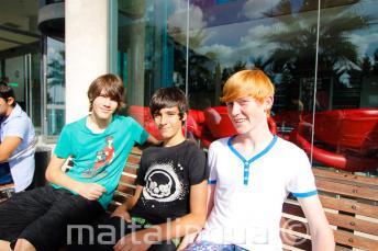 3 Sprachschüler sitzen auf einer Bank außerhalb der Residenz