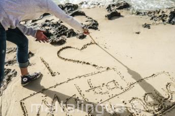 """Ein Sprachschüler schreibt """"Ich liebe dich Maltalingua"""" in den Sand"""