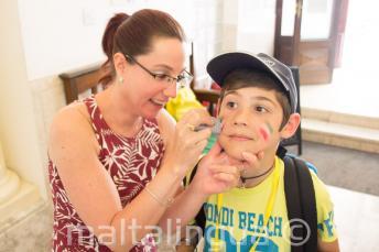 Eine Betreuerin schminkt ein Kind