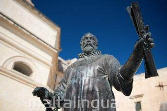 Eine Statue in Malta von einem Mann, der eine Schriftrolle hält