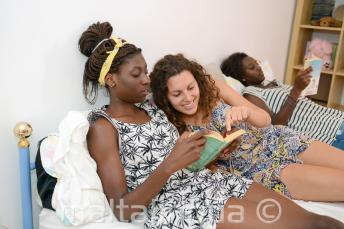 Eine Sprachschülerin liest zusammen mit einem Mitglied der Gastfamilie ein Buch