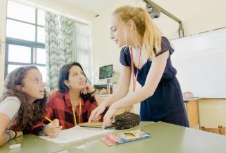 Lehrerin erklärt 2 Sprachschülerinnen etwas
