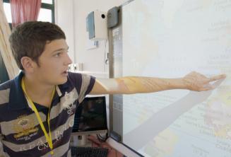 Ein junger Sprachschüler zeigt auf eine Karte im Sprachkurs