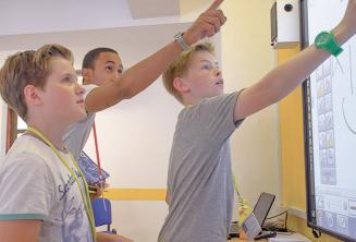 Ein Lehrer hilft 2 jungen Sprachülern am Whiteboard