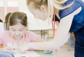 Eine Lehrerin hilft einem Kind im Englischkurs