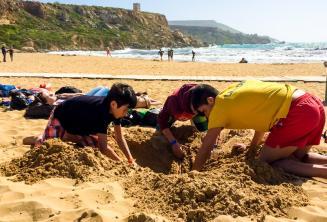 Gruppenleiter und Sprachschüler graben ein Loch am Strand