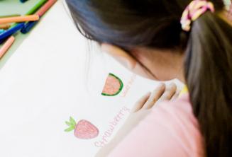 Eine junge Sprachschülerin malt und liest im Unterricht