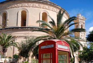 Eine rote Telefonzelle vor dem Mosta Rotunda