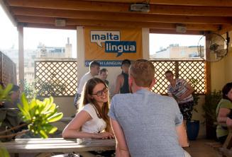 Englische Sprachschülerin spricht mit ihrem Lehrer auf der Dachterrasse