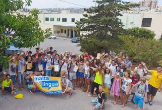 Große Gruppe Sprachschüler winkt auf dem Sommercampus
