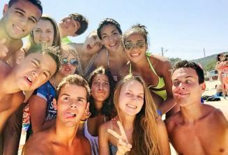 Sprachschüler schneiden am Strand Grimassen