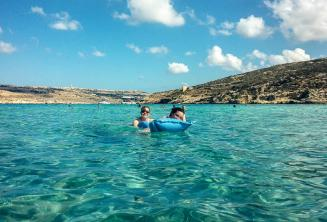 Sprachschüler schwimmen in der blauen Lagune in Comino
